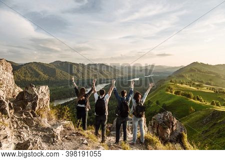 A Group Of Four People Hikers With Backpacks In The Mountains With Their Hands Up. Travel And Travel