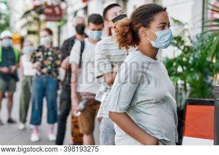 Young African American Woman Wearing Mask Waiting, Standing In Line With Other People, Respecting So