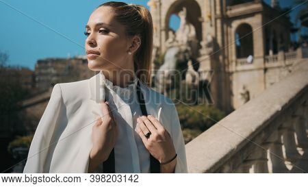 Portrait Of Posh Elegant Woman Confidently Looking Away On Stairs In City Park With Old Architecture