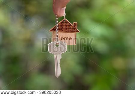 Home Key In Hand With House Keyring On Blur Green Garden Background, Copy Space