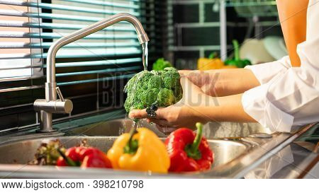 Woman Hands Washing Vegetables For Preparation Of Vegan Salad On The Worktop Near To Sink In A Moder