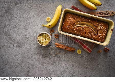 Wholegrain Banana Bread Freshly Baked On Grey Background With Banana, Cinnamon And Nuts. Bake Shop,