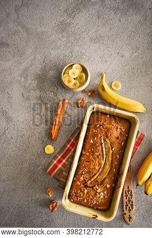 wholegrain Banana bread freshly baked on grey background with banana, cinnamon and nuts. bake shop, loaf, cafe, family baking concepts.