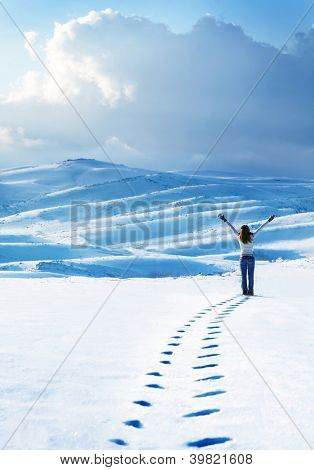 Happy woman jumping at winter mountains, active female enjoying nature, girl playing in the snow, teen having fun outdoor, healthy lifestyle and wintertime holidays vacation concept