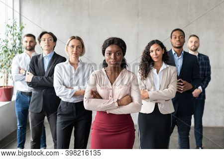 Determined Black Businesswoman Standing In Front Of Business Team Of Employees Looking At Camera Pos