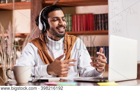 Online Teacher. Cheerful Indian Tutor Having Virtual Class Teaching Online Sitting At Laptop Compute