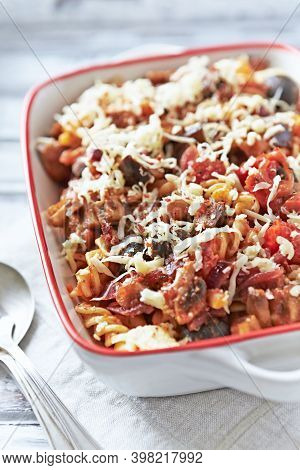 Pasta Gratin. Baked Fusilli Pasta With Cherry Tomatoes, Olives And Mozzarella Cheese. Bright Wooden