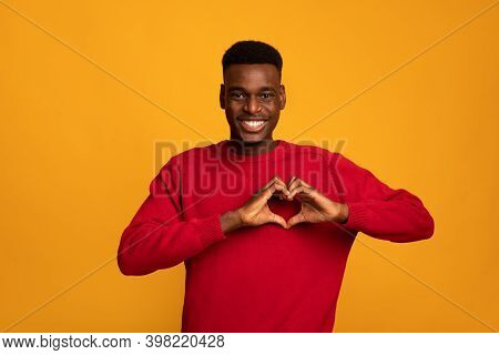 Kind Black Guy Shaping Hands Like Heart, Making Love Gesture Near Chest, Friendly African American M
