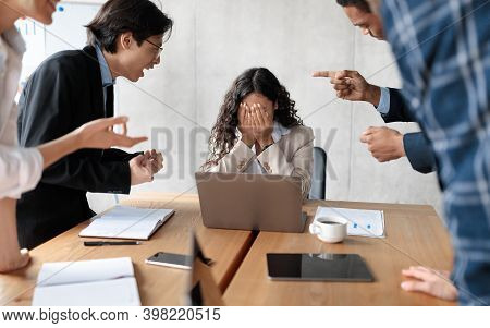 Workplace Conflict And Bullying. Aggressive Coworkers Yelling At Victimized Businesswoman Sitting At