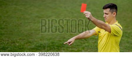 Angry Football Referee Showing A Red Card And Pointing With His Hand On Penalty