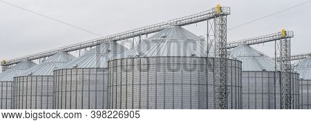 A Large Modern Plant For The Storage And Processing Of Grain Crops. Large Iron Barrels Of Grain. Sil