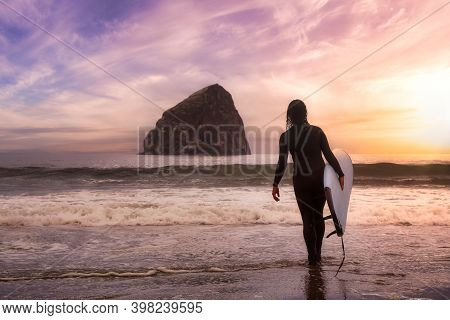 Adventurous Girl With A Surf Board Is Going Surfing In The Ocean. Colorful Sunset Sky. Taken In Paci