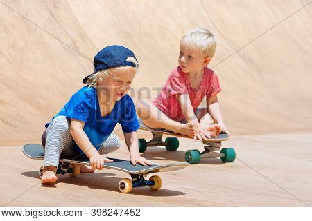 Funny Skateboard Riding. Little Children With Skateboards Have Fun In Beach Skate Park. Active Famil