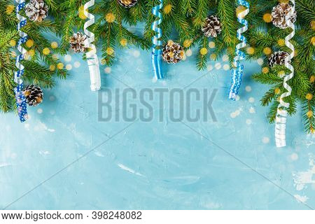 Christmas Or New Year Background With Green Fir Branches And Cones On Blue Background. Winter Concep