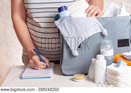 Unrecognizible Pregnant Caucasian Woman In Striped T-shirt Packing Big Blue Diaper Bag To Maternity