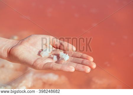 Boy's hand full of salt against of salty pink lake. Salt mining. Extremely salty pink lake, colored by microalgae with crystalline salt depositions in Torrevieja, Spain