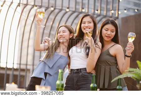Happy Young Asian Women Gang Drinking Champagne While Enjoying Rooftop Bar Party. Girls Best Friends