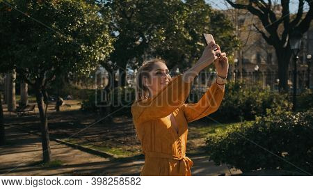 Young Beautiful Stylish Woman Taking Photo On Smartphone Walking In Park. Posh Lady Taking Selfie Ou