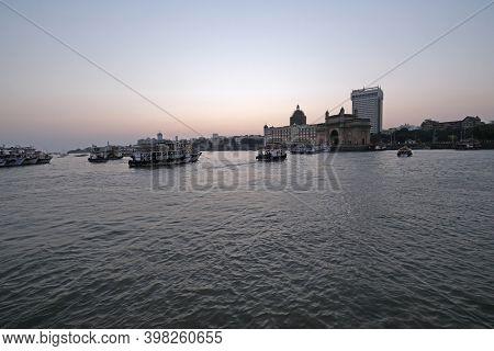 MUMBAI, INDIA - FEBRUARY 15, 2020: Taj Mahal hotel, Gateway of India and tourist boats in water of Arabian Sea on sunset in Mumbai, India