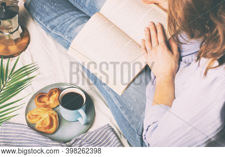 Young Woman Having Breakfast In Bed And Reading A Book