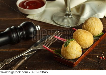 Arancini On A Rectangular Plate, Vintage Cutlery And Pepper Mill. Close-up, Italian Cuisine