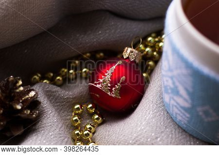Winter Christmas Background. Red Ball, Gold Beads, Pine Cones And Cup Of Tea. Christmas Still Life.