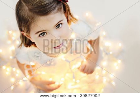 Cute, smiling, happy three years old girl sitting with glowing Christmas lights