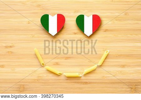 Pasta Smile And Heart-shaped Eyes In The Color Of The Flag Of Italy On A Wooden Background. Concept