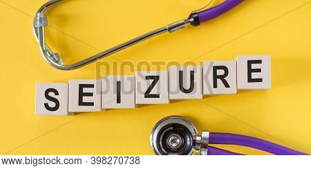 The Word Seizure From Wooden Cubes On Yellow Table With Stethoscope.