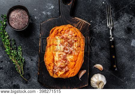 Baked Sweet Potato Yam Stuffed With Ground Beef And Cheese. Black Background. Top View