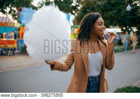 Cheerful woman with cotton candy in amusement park