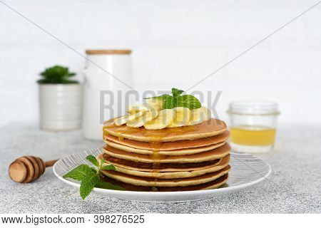 Pancakes With Honey And Bananas For Breakfast On The Kitchen Table.