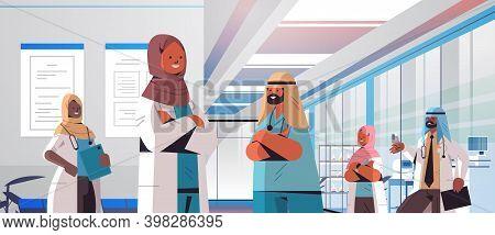 Team Of Arabic Doctors In Uniform Discussing During Meeting In Hospital Corridor Medicine Healthcare