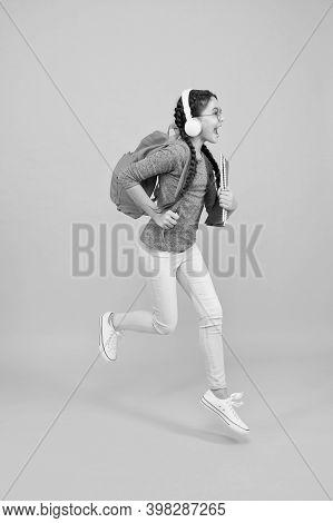 Full Of Energy. Energetic Child Run To School. Happy Girl In Motion Yellow Background. Childhood Ene