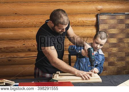 Father And Son Together Make A Wooden Birdhouse In The Workshop. Cheerful Father With A Little Boy D