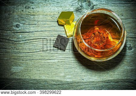 Cognac Snifter And Chocolate On Old Wooden Background Top View. Old Fashioned Whiskey Or Scotch Glas