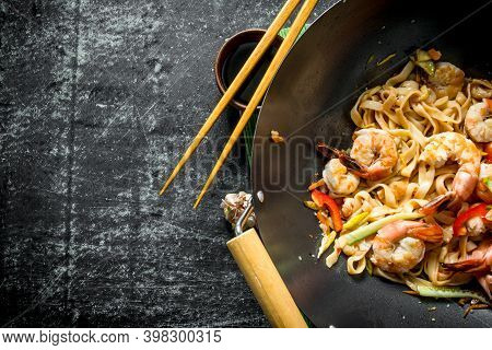 Chinese Wok. Udon Noodles In A Wok Pan With Shrimp And Sauce. On Dark Rustic Background