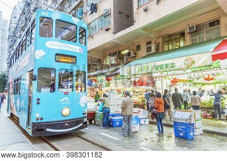 Hong Kong, China - February 15, 2019 : Tram Passing Through Busy Street Market In Hong Kong. Tram Is