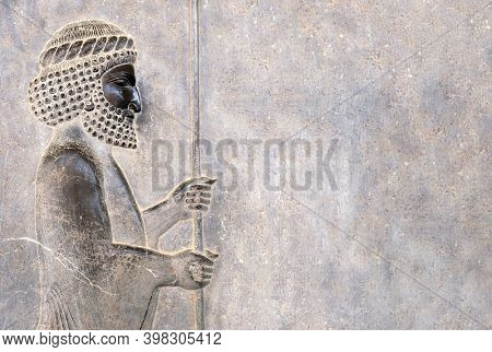 Ancient wall with bas-relief - assyrian warrior with spear, Persepolis, Iran. UNESCO world heritage site. Horizontal background with embossed image persian bearded man. Copy space for text
