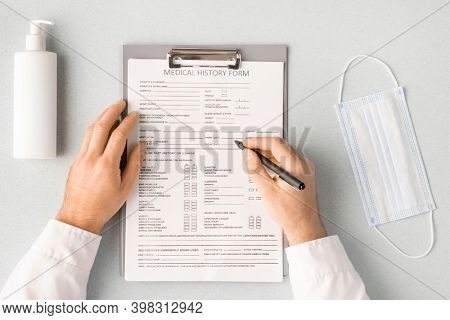 Overview of hands of clinician with pen over medical history form filling in personal information of patient with mask and sanitizer near by