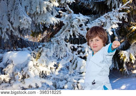 Huge spruce covered with snow. Winter coniferous forest. Handsome boy in white judo uniform training for judo. New Years is soon