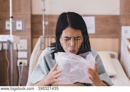 Asian Woman Patient Puke Or Vomiting Into Plastic Bag At Hospital,nausea,indigestible