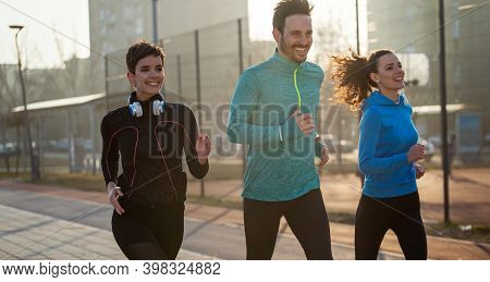 Jogging And Running Are Fitness Recreations. Happy Group Of Friends Exercising Together.