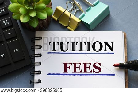 Tuition Fees Words Is Written In A Notebook With A Marker, Calculator, Clamps And Cactus. Business A