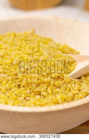 Bulgur In A Wooden Bowl On The Background Of A Wooden Table, Rustic Style. Bulgur Wheat Grains
