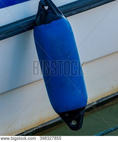 Blue Fender Buoy Hanging Of The Side Of A Ship. Close Up.