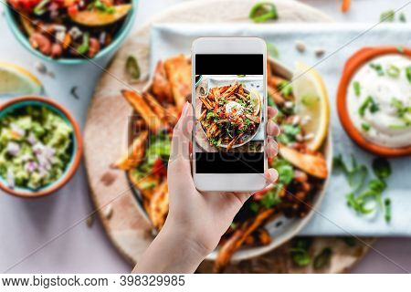 Hand Taking A Photo Of Healthy Food With Smartphone. Woman Using Phone Mobile Apps Make Digital Pict