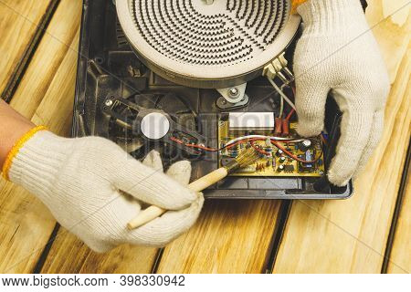 Electric Stove Service. Hands In White Gloves With A Brush Remove Dust From The Electric Stove. The