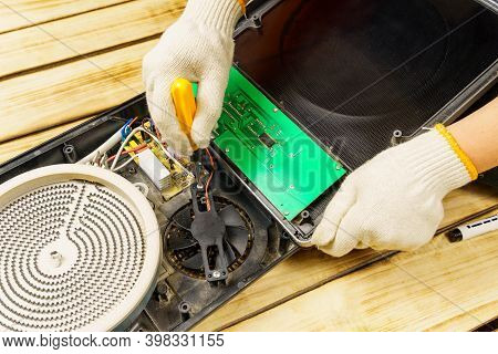 The Master Unscrews Or Screws The Fan To The Electric Stove With A Screw. A Hand In A White Glove Ho