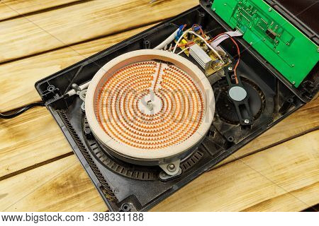 Close-up Of An Open Electric Stove And A Heated Spiral In It On A Wooden Background. Red Heating Ele
